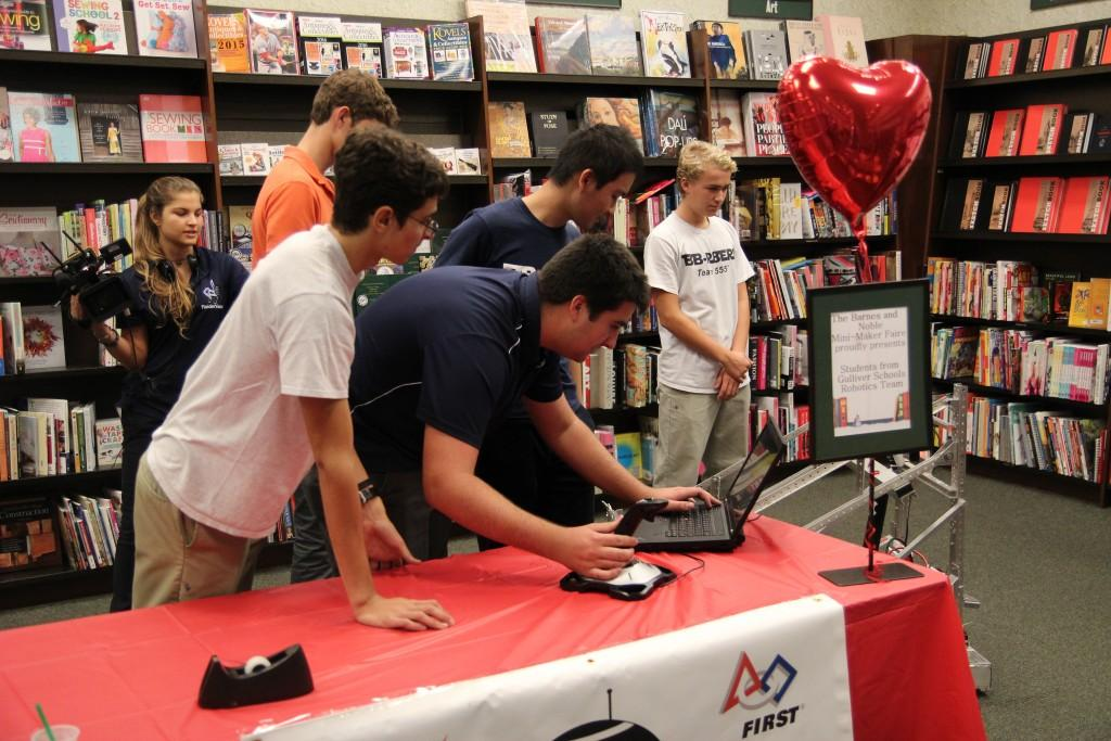 Senior Louis Hamilton and Junior Rene Carballo demonstrate last year's robot and how it worked. They were presenting in front of children at a convention at Barnes and Noble at Sunset Place.  Photo by Tyler Perez.