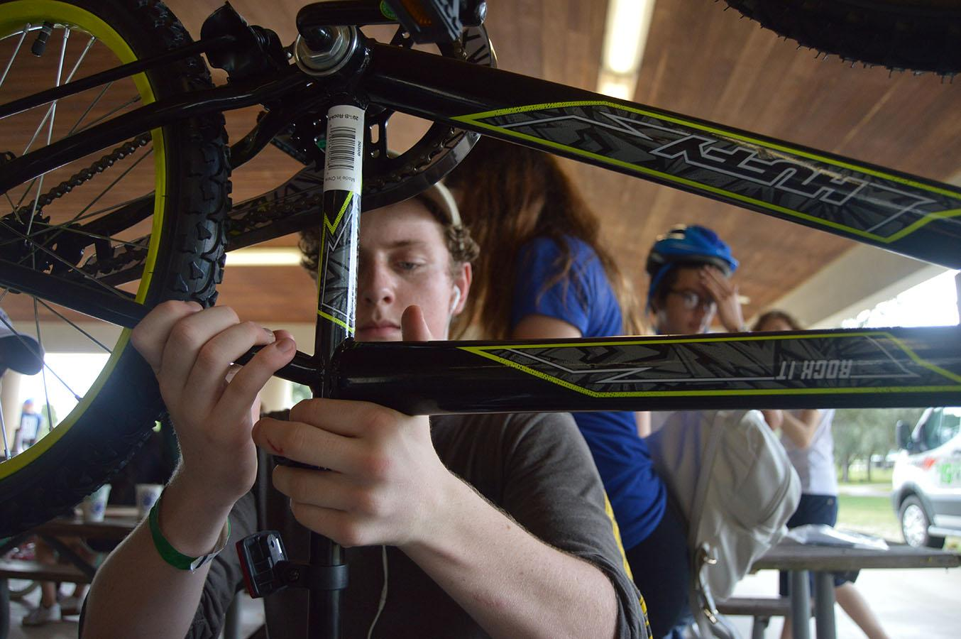 Sophomore Christopher McCormick works on his bike during the sophomore class activities on Nov. 13 at C.B. Smith Park.  The bikes were donated to Toys for Tots.  Afterwards, the class played a variety of games and engaged in team-building activities.  Photo by Pedro Schmeil.