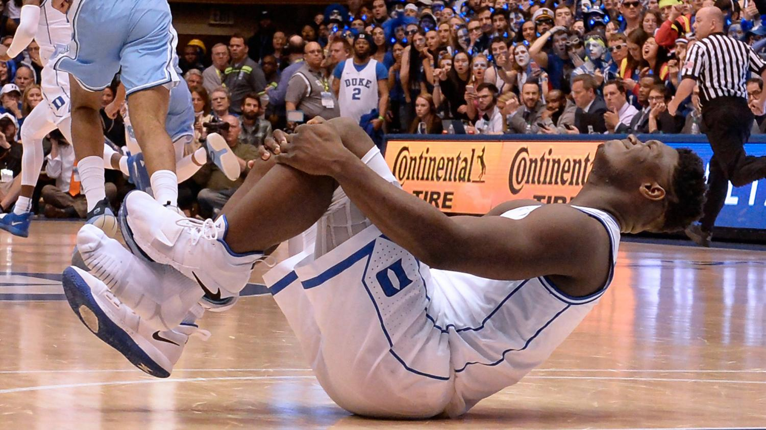 Duke forward Zion Williamson holds his knee after injuring himself and damaging his shoe during the opening moments of the game in the first half on Wednesday, Feb. 20, 2019, at Cameron Indoor Stadium in Durham, N.C. (Chuck Liddy/Raleigh News & Observer/TNS)