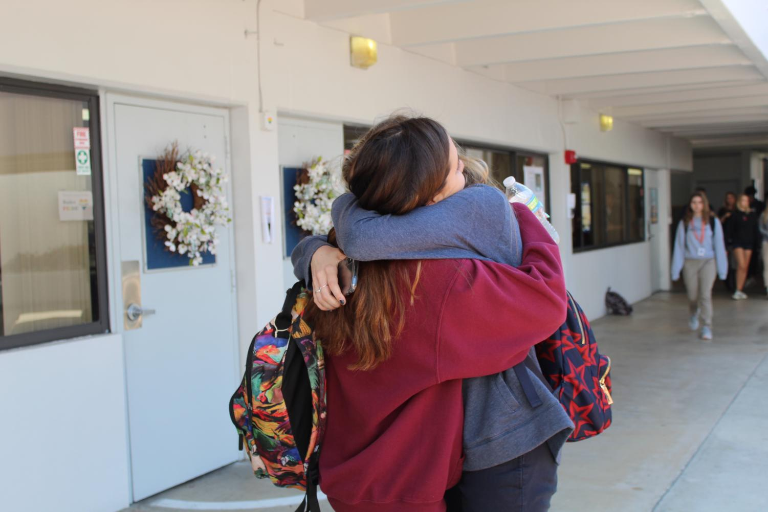 Students hug one another as they pass each other in the halls yesterday as they left the schoolwide morning assembly in memory of sophomore Javier Cañedo. Signs of support were evident throughout the day, with students writing notes and spray painting messages on the Sean Taylor Memorial Field. Photo by Olivia Martin-Johnson.