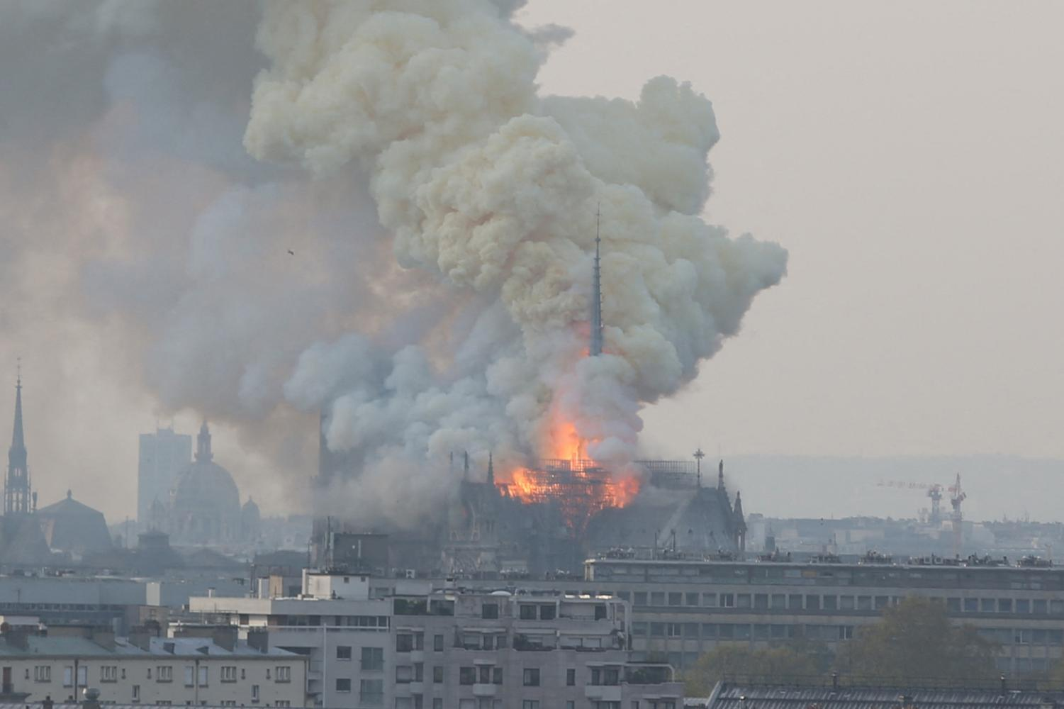 Smoke and flames rise during a fire at the landmark Notre Dame Cathedral in central Paris, France on Monday, April 15, 2019, potentially involving renovation works being carried out at the site, the fire service said. (Jerome Domine/Abaca Press/TNS)