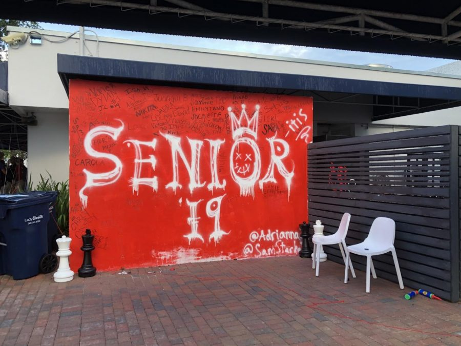 Students+were+greeted+by+a+red+senior+wall+on+the+morning+of+May+2+in+the+area+outside+of+the+cafeteria.+This+was+one+of+the+the+results+of+the+senior+%22prank.%22+Seniors+had+permission+to+paint+the+wall+and+sign+their+names.+Photo+by+Laura+Attarian