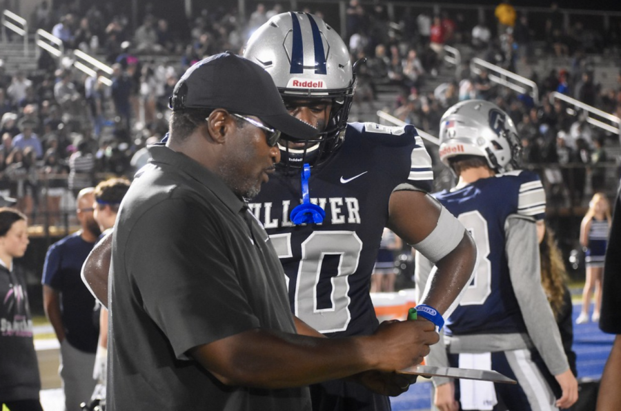 Sophomore defensive end, Bakari Edwards and defensive coordinator, Derrick Lordeus gameplan and fix mistakes on the sideline. Photo by Jen Uccelli.