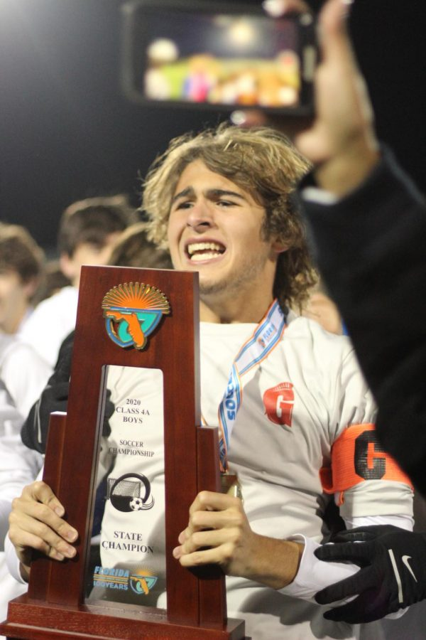 Senior, Juan Lazcano is filled with a variety of emotions as he holds the state champioship trophy at the end of the game. He remembers all the hard work and effort he put in and realizes it is all worth it. Photo by Julian Concepcion.