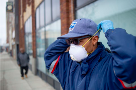Flint postal worker Mark Fransioli delivers mail wearing gloves and a mask on Monday, March 23, 2020 in Flint. All Michigan residents and most businesses are required to stay in their homes under an executive order issued by Gov. Gretchen Whitmer to slow the spread of the coronavirus COVID-19.