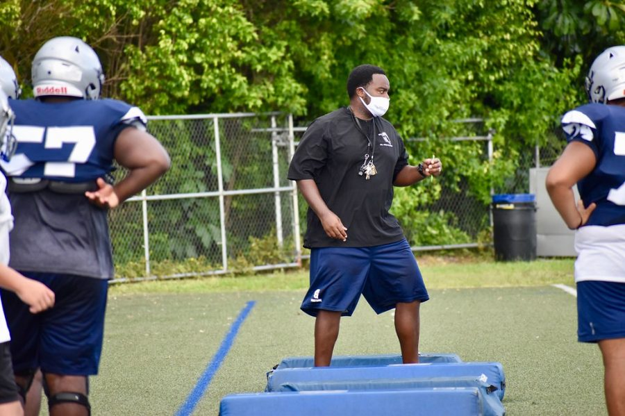 Coach Earl Sims wears a mask to train football players on Sept. 18.