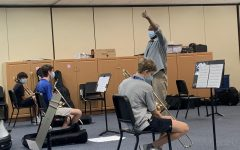 Music Director Rufus Jones conducts hybrid band rehearsal. The Music Department is one of the most impacted groups at school, as it is difficult to keep audio in sync and practice instruments when some students are online and some are in person.