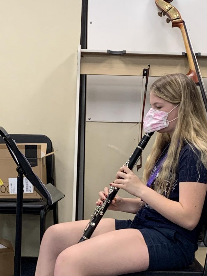 A music student plays her instruments during class. Students with instruments like the clarinet must wear masks while playing.