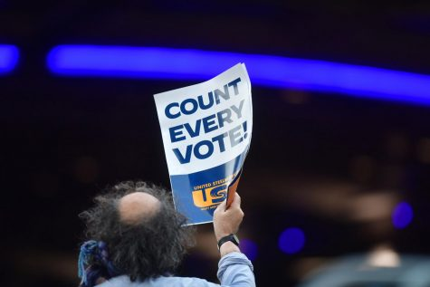 """A man holds a placard that reads """"Count Every Note"""" while demonstrating across the street from supporters of President Donald Trump outside of where votes are still being counted in Philadelphia, six days after the general election on November 9, 2020."""