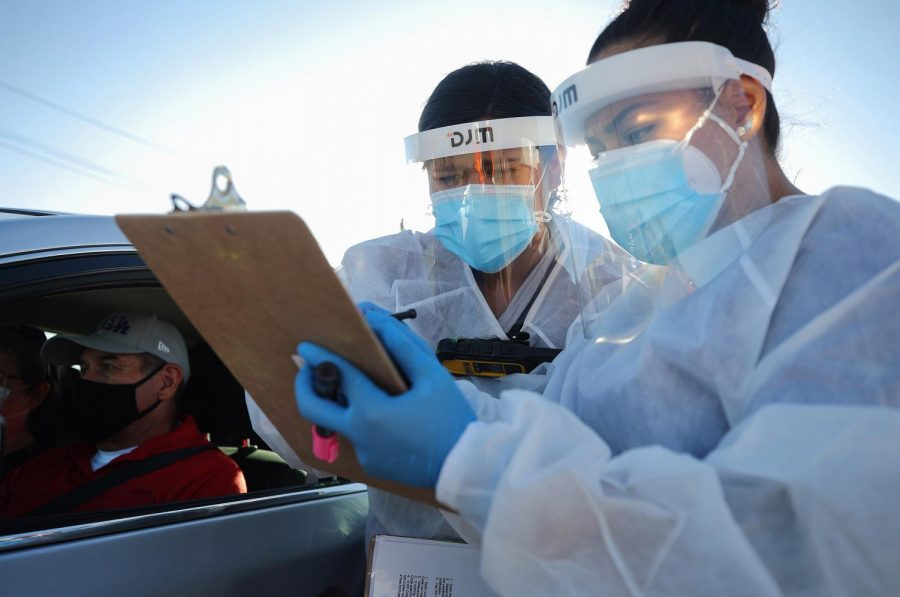 Frontline healthcare workers check information at a COVID-19 testing site in El Paso, Texas, on Nov. 13, 2020. Now in late December, Texas is surpassing the record hospitalizations they saw in July.