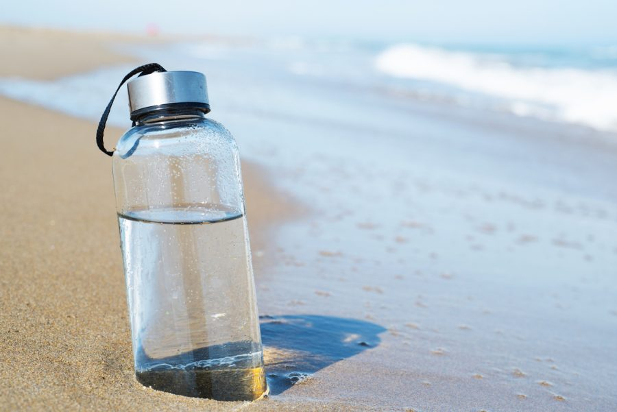 closeup of a glass reusable water bottle on the seashore of a lonely beach