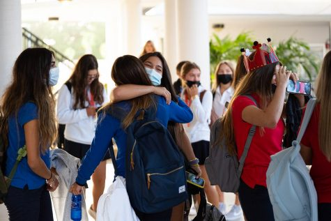 Students embrace as they arrive to campus on the first day of school. For some students, a year and a half went by before they could see their friends in-person at school.