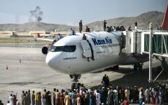 Afghan people climb atop a plane as they wait at the Kabul airport in Kabul, Afghanistan, on Aug. 16, 2021.