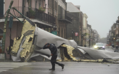 A man passes by a section of roof that was blown off of a building in the French Quarter by Hurricane Ida winds, Sunday, Aug. 29, 2021, in New Orleans.