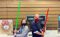 Senior Caroline Isom, president of the new Saber Craft Choreography Club,  wields her lightsaber with anthropology teacher Mario Cubas, one of the clubs sponsors.