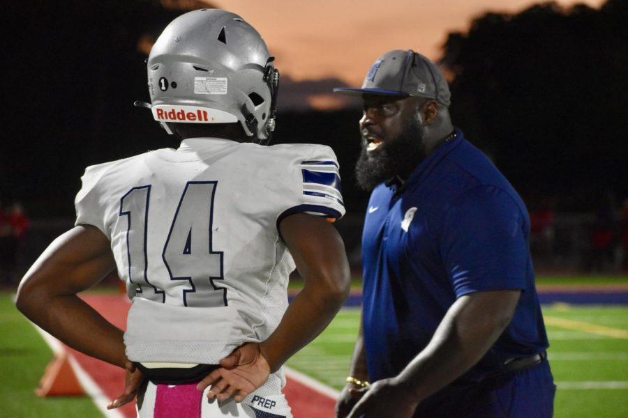 Junior Sedrick Irvin listens as Assistant Coach Larry Fitts addresses the football team at the Chaminade game on Oct. 16.
