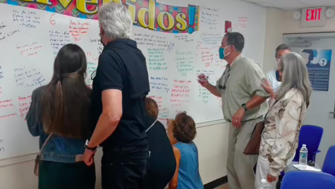Parents write on the welcome wall during Back-to-School Night.